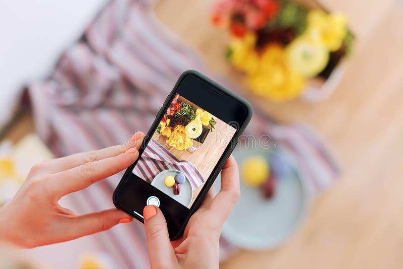 Mulher que toma a foto das flores e dos bolinhos de amêndoa com smartphone Conceito blogging da oficina da fotografia de Instagra fotografia de stock