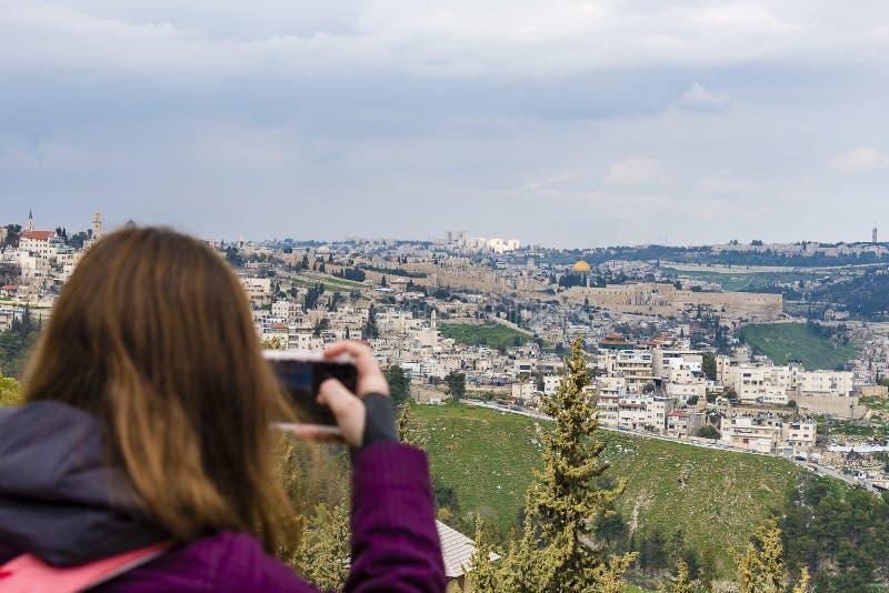 Mulher que toma a fotografia com o smartphone em apreciar a vista da fotografia do Jerusalém na cidade velha do telefone do Jerus imagens de stock royalty free