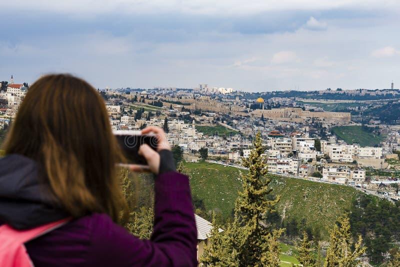 Mulher que toma a fotografia com o smartphone em apreciar a vista da fotografia do Jerusalém na cidade velha do telefone do Jerus fotos de stock