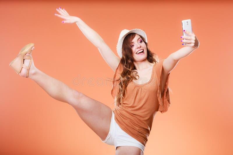 Mulher que toma a imagem do auto com câmera do smartphone imagens de stock royalty free