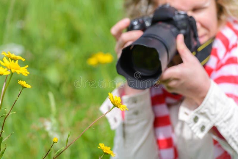 Mulher que toma imagens com uma câmera de SLR imagens de stock