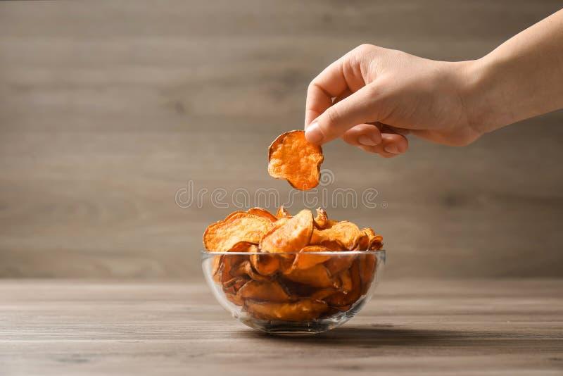 Mulher que toma a microplaqueta de batata doce da bacia na tabela fotografia de stock royalty free