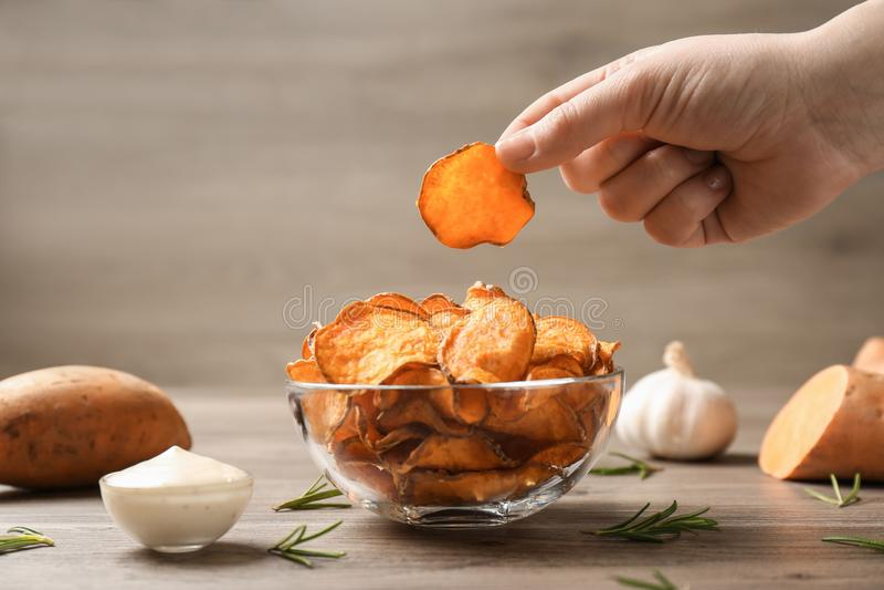 Mulher que toma a microplaqueta de batata doce da bacia na tabela fotos de stock royalty free