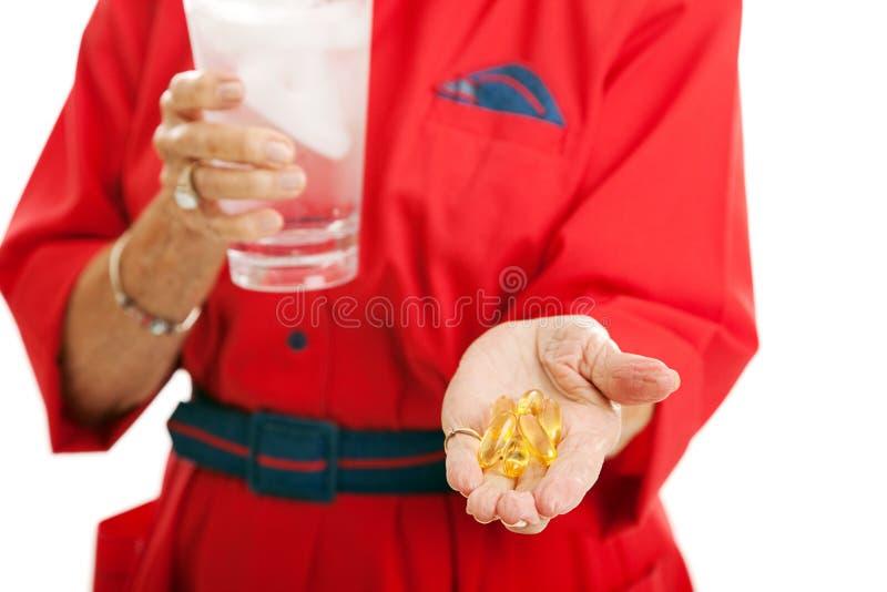 Mulher que toma o óleo de peixes da ômega 3 fotos de stock