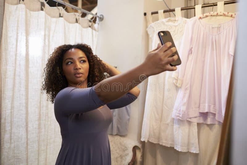 Mulher que toma o selfie em uma sala de mudança do boutique fotografia de stock royalty free