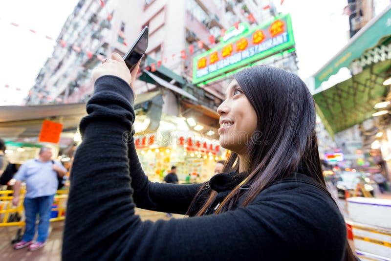 Mulher que toma o selfise no mercado de rua foto de stock