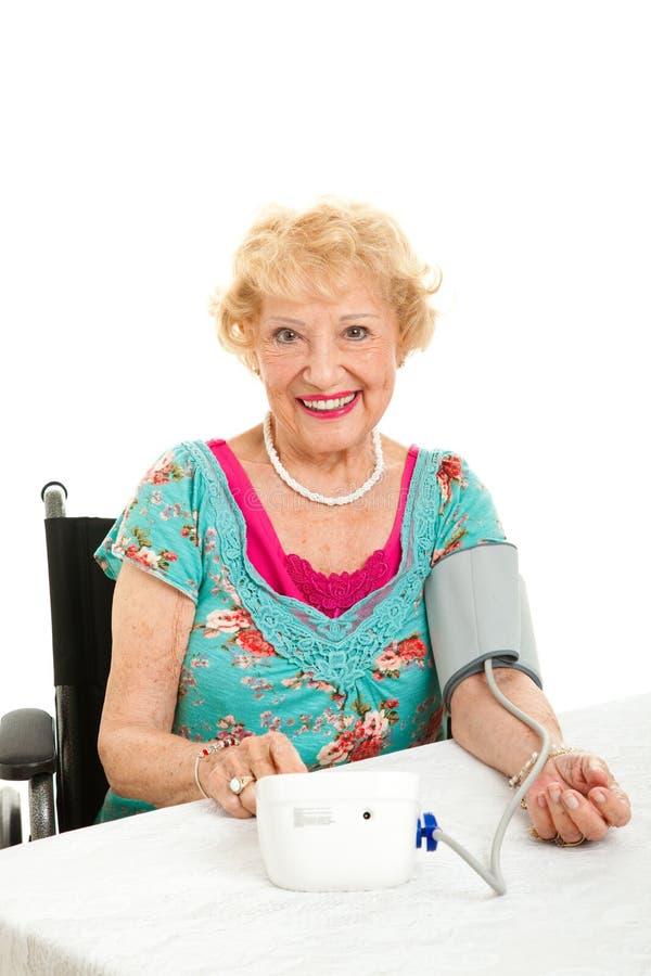 Mulher que toma sua própria pressão sanguínea