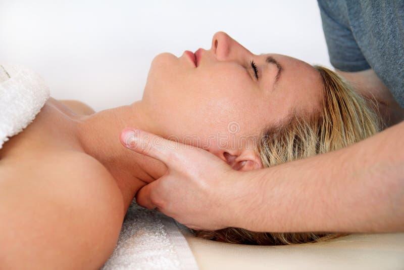 A mulher que toma um pescoço da massagem muscles na tabela da massagem foto de stock royalty free