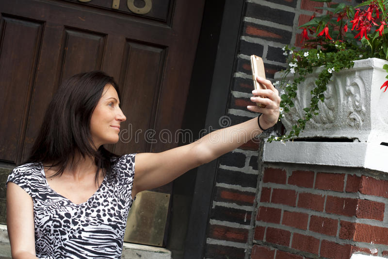 Mulher que toma um selfie na frente de sua porta imagem de stock royalty free