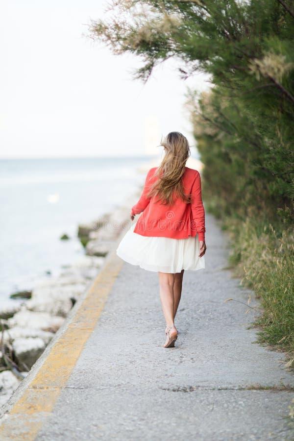 Mulher que toma uma caminhada de relaxamento no mar fotos de stock