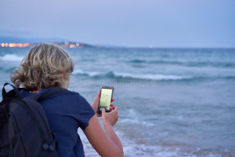Mulher que toma uma foto de um mar no telefone esperto no por do sol fotografia de stock