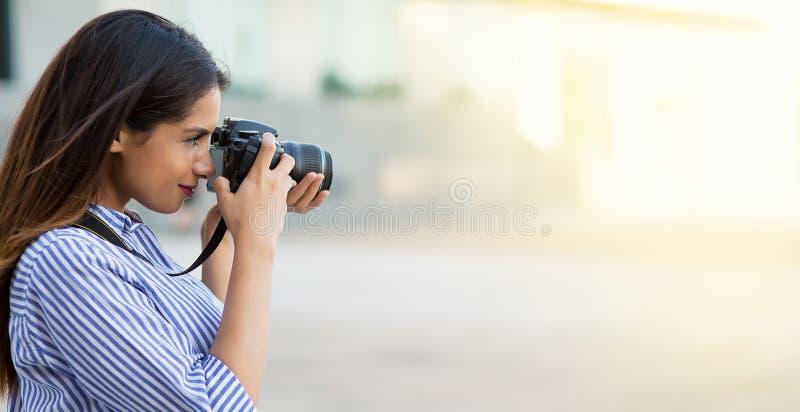 Mulher que toma uma foto usando a câmera profissional Fotógrafo novo, luz natural Copie o espa?o fotografia de stock royalty free