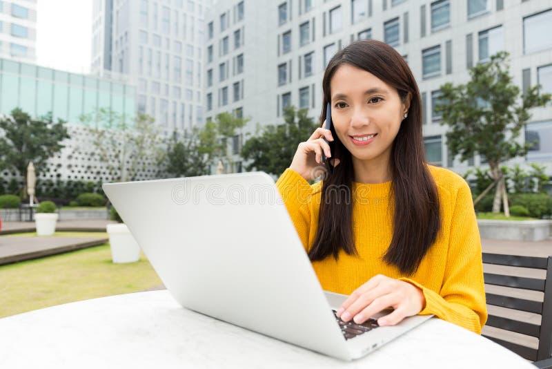 A mulher que trabalha com laptop e faz uma chamada usando o mo fotos de stock royalty free