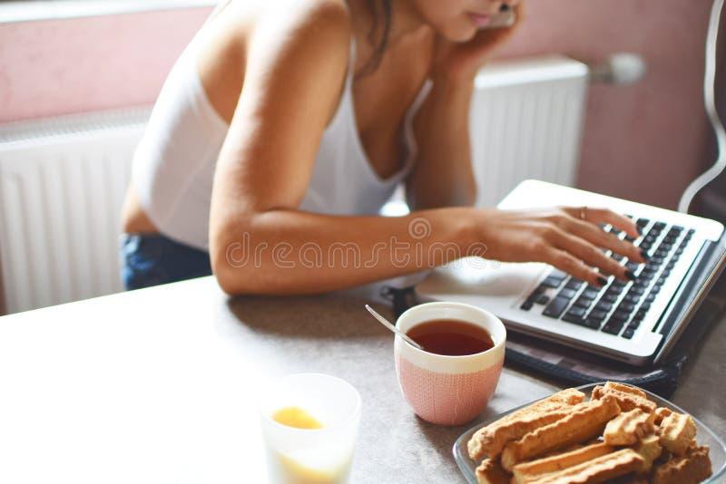 Mulher que trabalha com o portátil na cozinha fotografia de stock