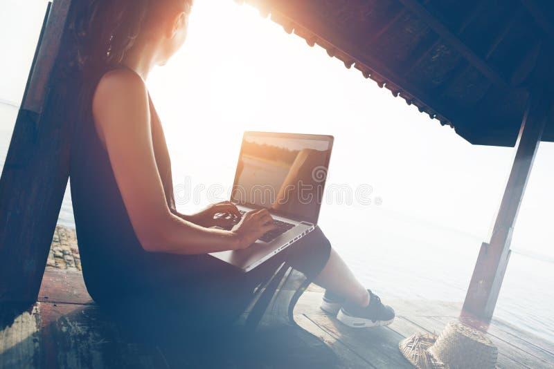 Mulher que trabalha com o portátil na praia no abrigo da sombra imagem de stock royalty free