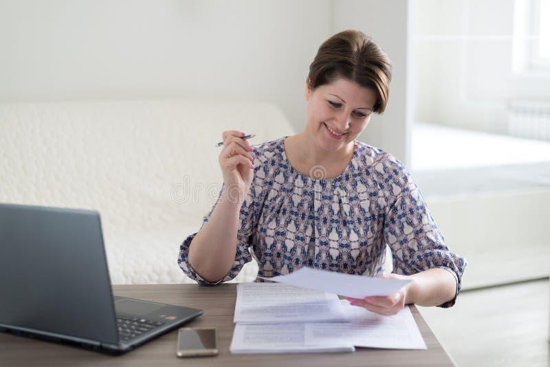 Mulher que trabalha com os originais que olham o portátil imagens de stock royalty free