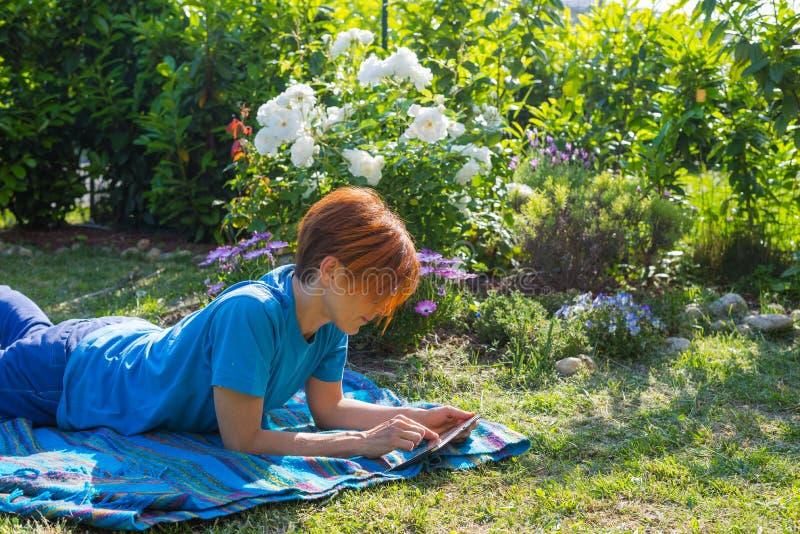 Mulher que trabalha com tabuleta fora no jardim florido imagem de stock royalty free