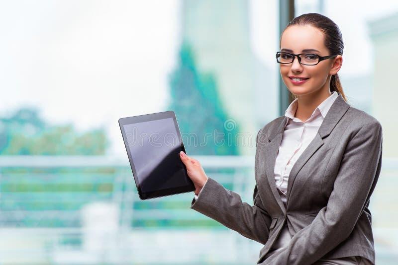 A mulher que trabalha com a tabuleta no escritório imagem de stock