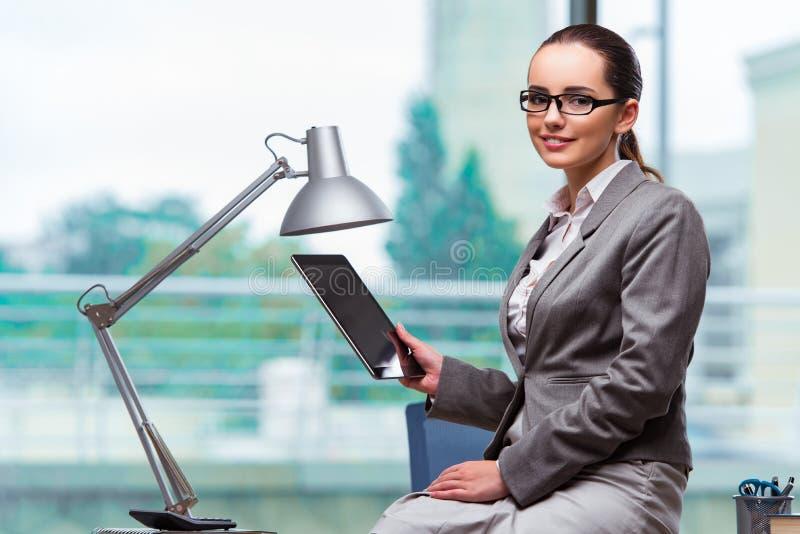 A mulher que trabalha com a tabuleta no escritório fotografia de stock