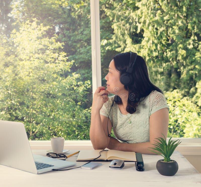 Mulher que trabalha em casa ao olhar para fora na luz do dia brilhante de imagem de stock royalty free