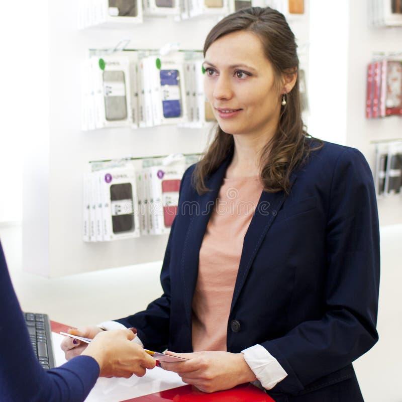 Mulher que trabalha em uma loja da eletrônica imagens de stock