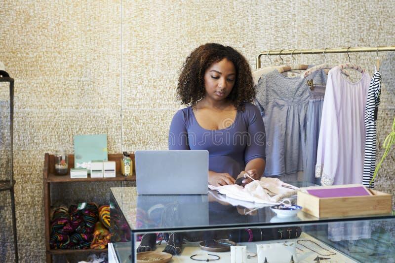 Mulher que trabalha na loja de roupa que verifica o preço, vista dianteira fotografia de stock royalty free