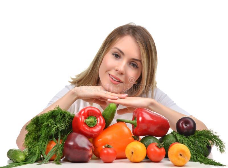 Mulher que trabalha na mesa com o SMI feliz das frutas e legumes frescas imagem de stock royalty free