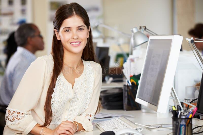 Mulher que trabalha na mesa no escritório criativo ocupado fotografia de stock