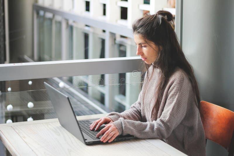 Mulher que trabalha nas mãos do café no portátil do teclado fotografia de stock royalty free