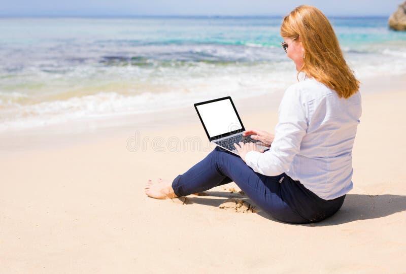 Mulher que trabalha no computador ao relaxar na praia fotos de stock royalty free