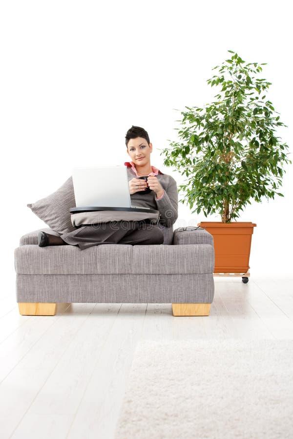 Mulher que trabalha no computador em casa imagem de stock
