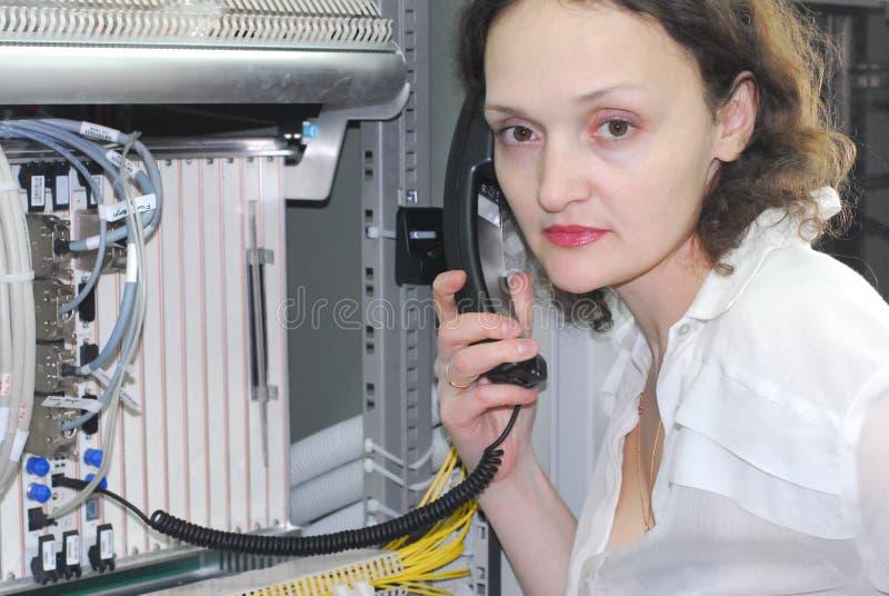 Mulher que trabalha no equipamento de telecomunicação imagens de stock