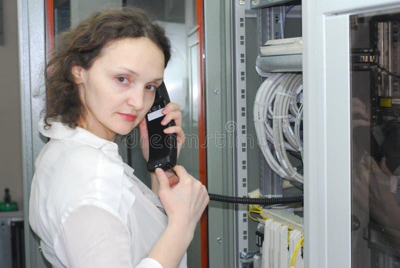 Mulher que trabalha no equipamento de telecomunicação fotos de stock
