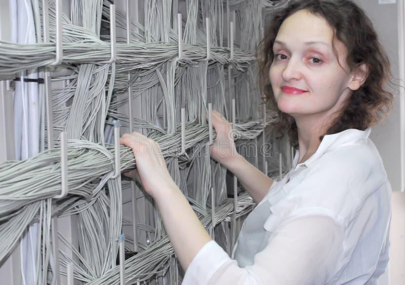 Mulher que trabalha no equipamento de telecomunicação fotografia de stock