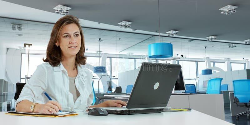 Mulher que trabalha no escritório moderno fotografia de stock royalty free