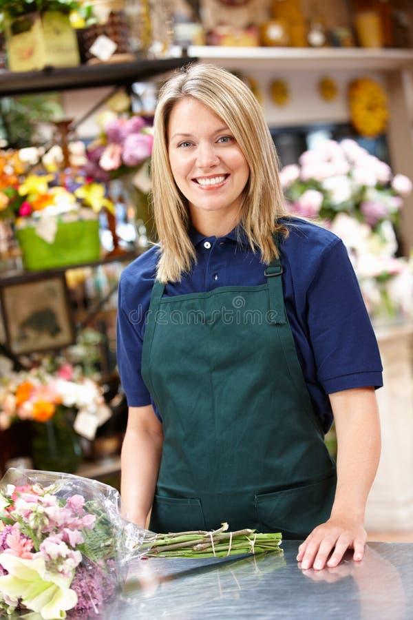 Mulher que trabalha no florista imagem de stock