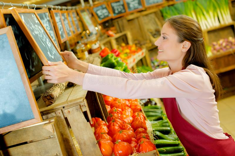 Mulher que trabalha no greengrocery foto de stock