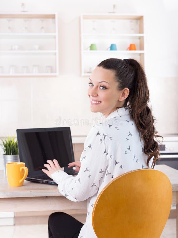 Mulher que trabalha no portátil da casa fotos de stock