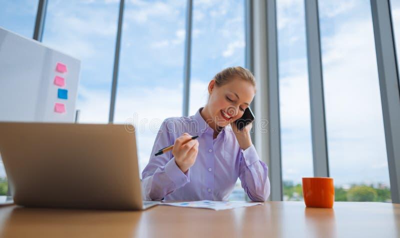 Mulher que trabalha no portátil no escritório ao falar no telefone, retrato da mulher de negócios fotografia de stock
