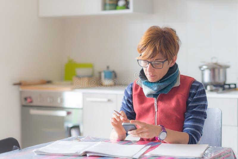 Mulher que trabalha originais em casa, da leitura e da escrita imagens de stock royalty free
