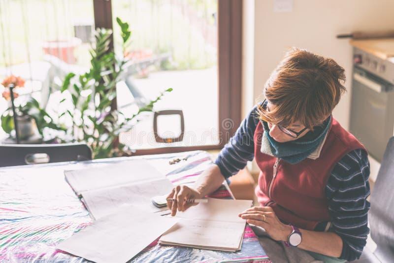 Mulher que trabalha originais em casa, da leitura e da escrita imagens de stock