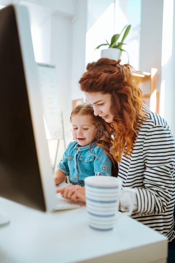 Mulher que trabalha remotamente passando o tempo com sua filha bonita imagem de stock royalty free