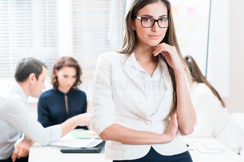 Mulher que trabalham no escritório e grupo que tem a reunião de negócios foto de stock