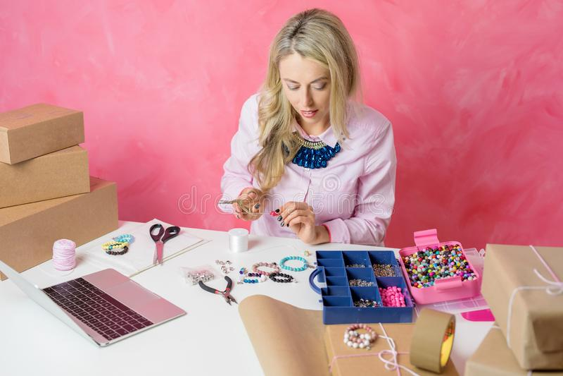 Mulher que transforma seu passatempo na empresa de pequeno porte Fazendo a joia em casa e vendendo a em linha imagem de stock