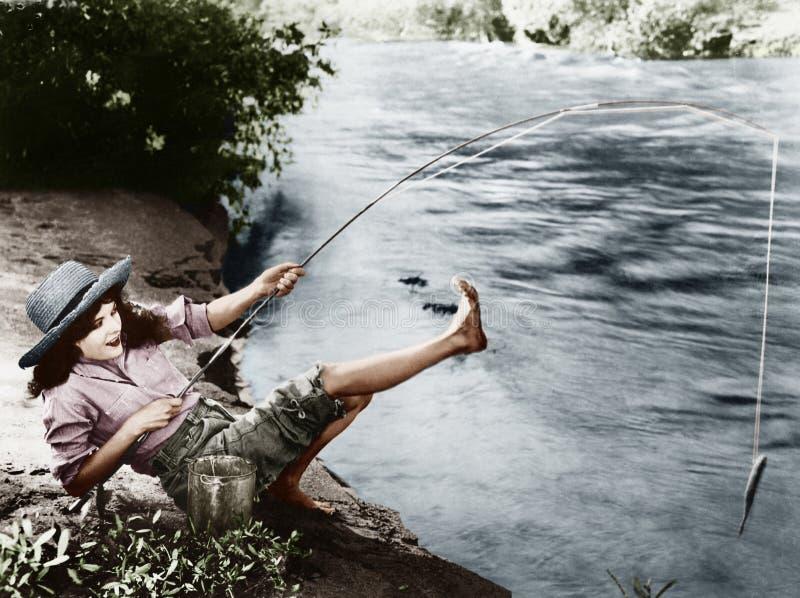 A mulher que travou um peixe pequeno que cai sobre para trás (todas as pessoas descritas não é uma viva mais longo e nenhuma prop imagem de stock royalty free