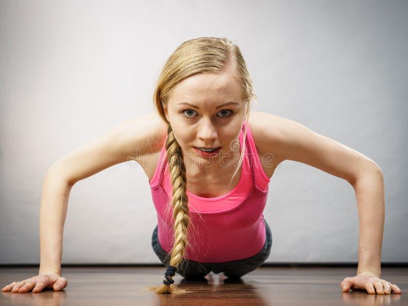 A mulher que treina em casa fazer empurra levanta fotografia de stock