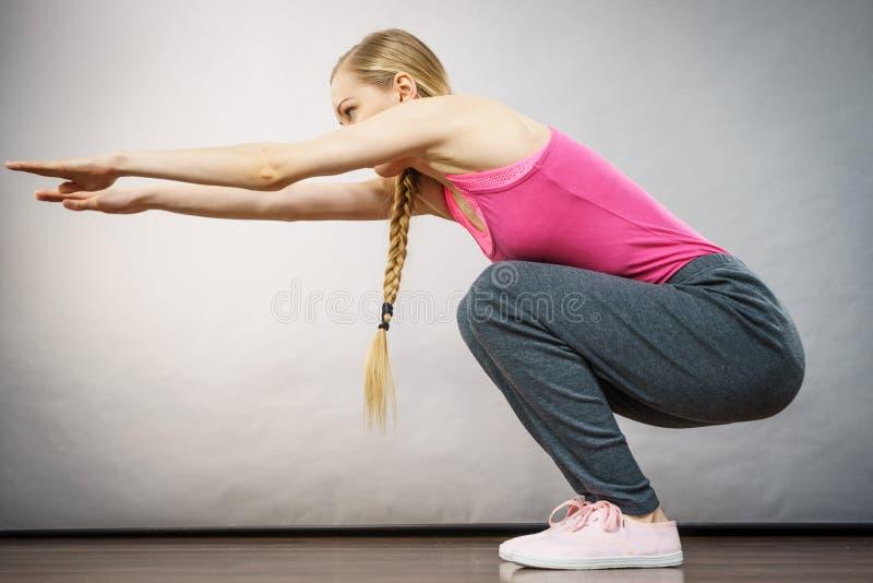 A mulher que treina em casa fazer senta-se levanta ocupas fotografia de stock royalty free