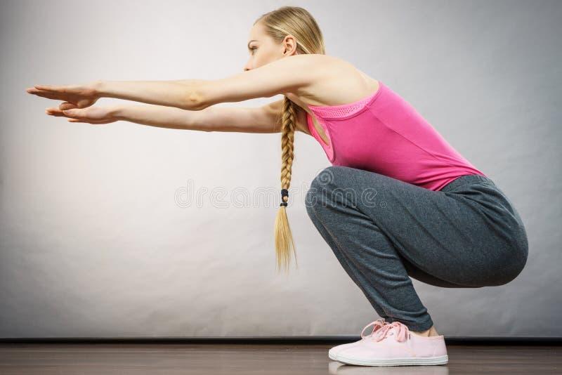 A mulher que treina em casa fazer senta-se levanta ocupas imagem de stock royalty free
