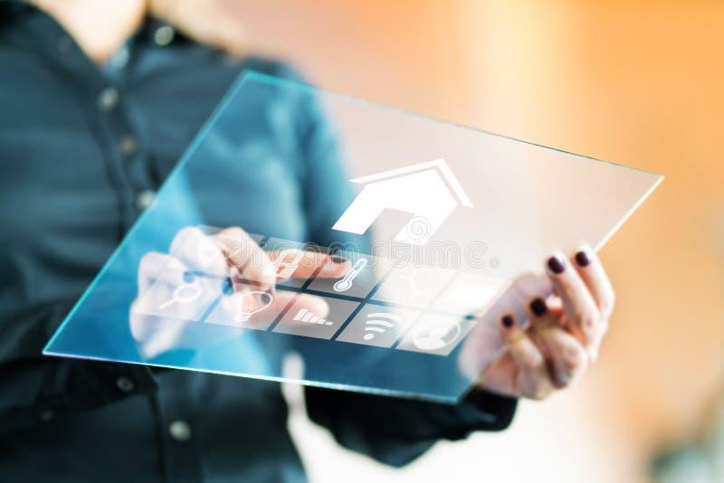 Mulher que usa a aplicação esperta do controle da casa com a tabuleta de vidro transparente futurista imagem de stock