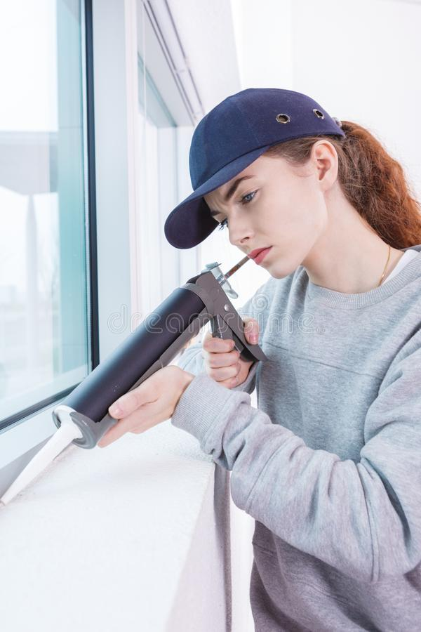 Mulher que usa a arma de calafetagem fotografia de stock
